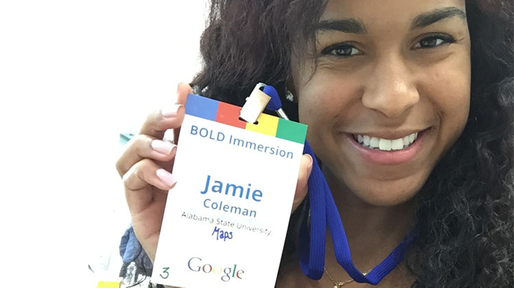 Jamie Coleman smiles while holding up her Google badge during her summer internship.