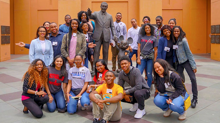 HBCU In LA Internship participants poses in front of a statue of Walt Disney Holding Mickey's hand at the Walt Disney Animation Studios in Burbank, CA during the HBCU Hollywood Welcome week.