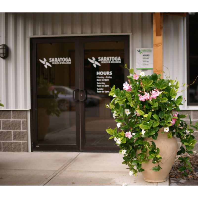 Saratoga Springs gym entrance flanked by beautiful mandevilla planters into the friendly welcoming atmosphere