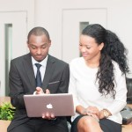 African american man and woman looking at a MacBook