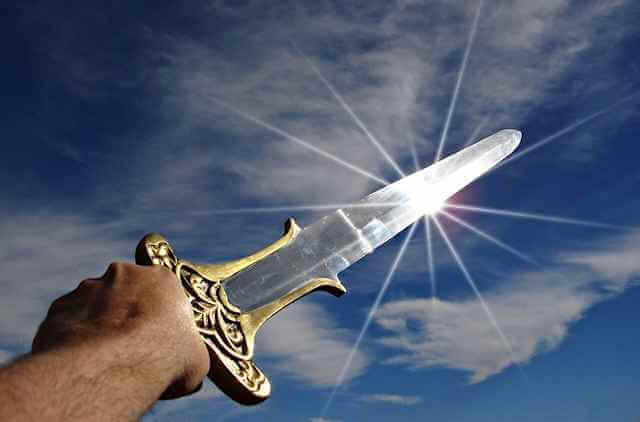 Picture of person holding up a shining sword towards the sky