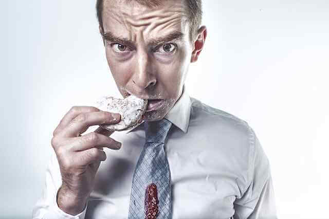 Frightened man holding messy snack to mouth