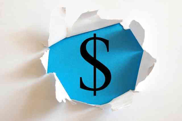 Picture of money sign through a torn hole in paper. This Obamacare flaw may end being a windfall to many taxpayers on the insurance exchanges...