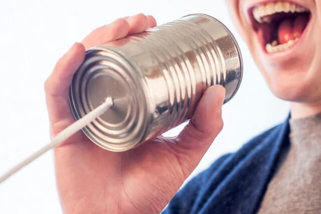 Picture of a man, with a wide and open mouth speaking into a stringed can. Having a Big Mouth can lead to BIG healthcare savings!