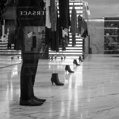 A security guard is standing in line with 4 pair of expensive shoes that are place in a one on the floor. Above each pair of shoes are clothing racks so that it looks like the shoes could be paired with th outfit.