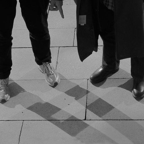 Two men ,heads not showing, are standing at right angles to each other. The sun and a reflection of the sun provide shadows of the legs that look like a tartan or a hopscotch on ground in front of them. As soon as they move the shadows will change, hence the transient hopscotch .