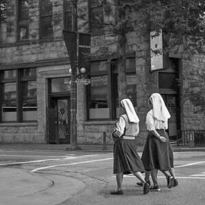 Image by Teresa Hogarth Photography of 3 nuns strolling across the crosswalk in Eastside of Vancouver. One is counting her rosary.
