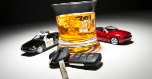 A glass of liquor with a set of car keys