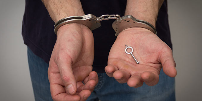 Expunge or seal an arrest record in Tampa, Florida. Male with handcuffs on.