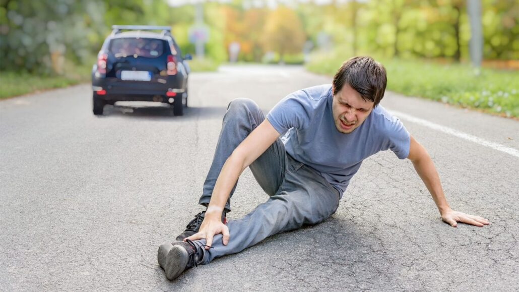 Man hit by a car on the road grabbing his foot in pain