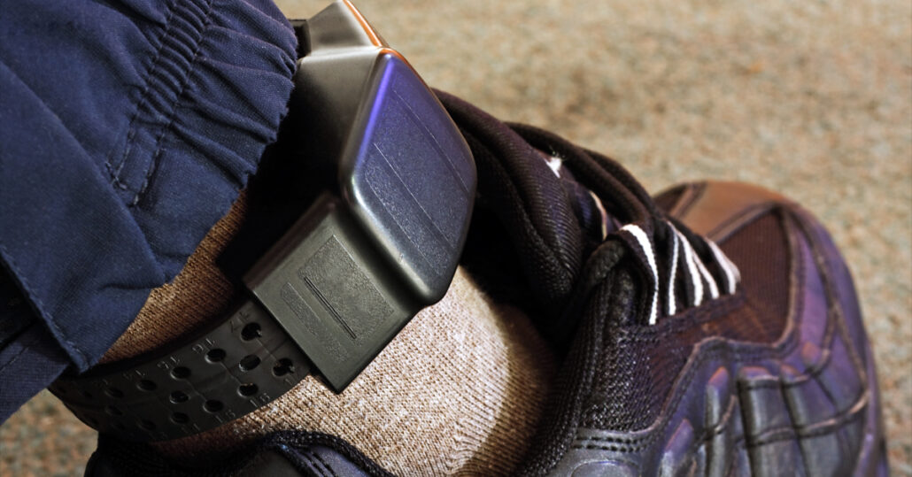 Closeup of a man wearing a house arrest bracelet on ankle
