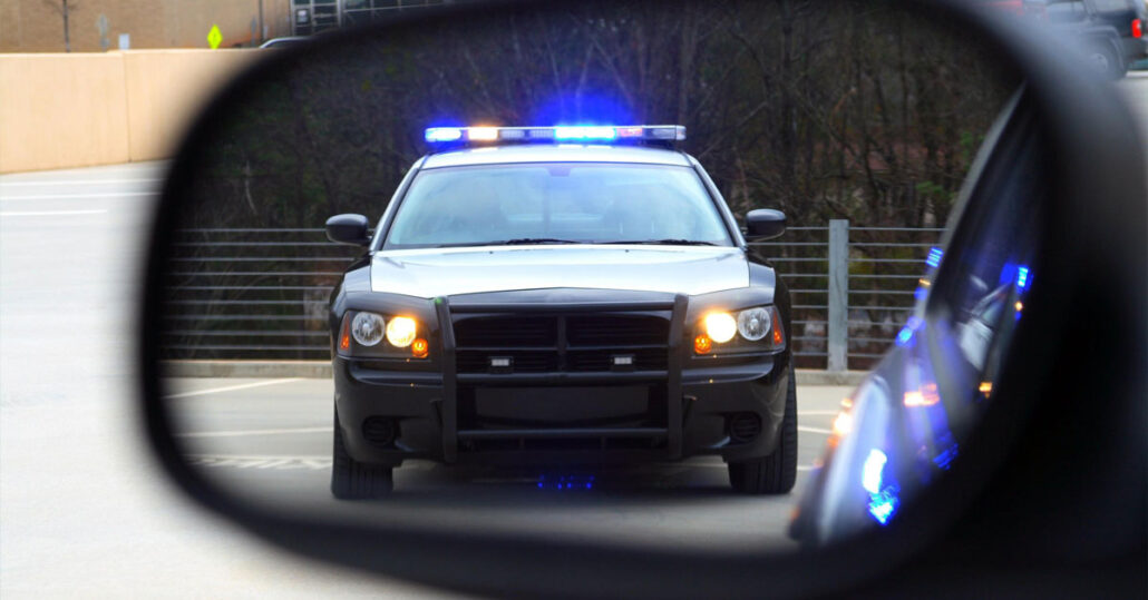 Police car with its lights on in a rearview mirror