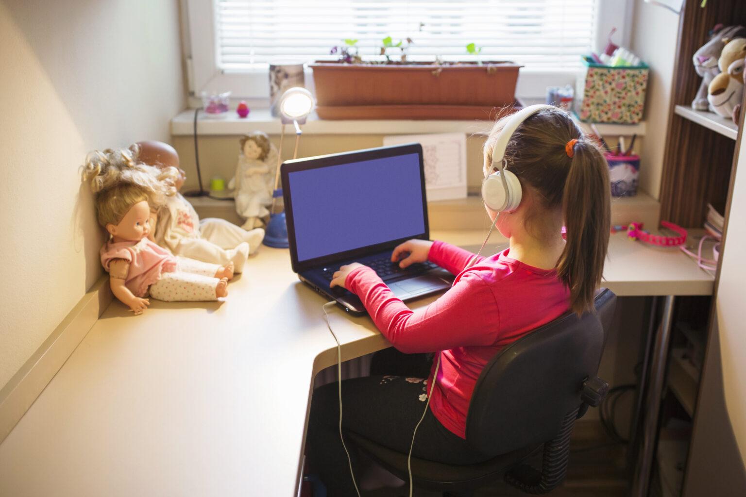 Menina com fone de ouvido na frente do computador estudando
