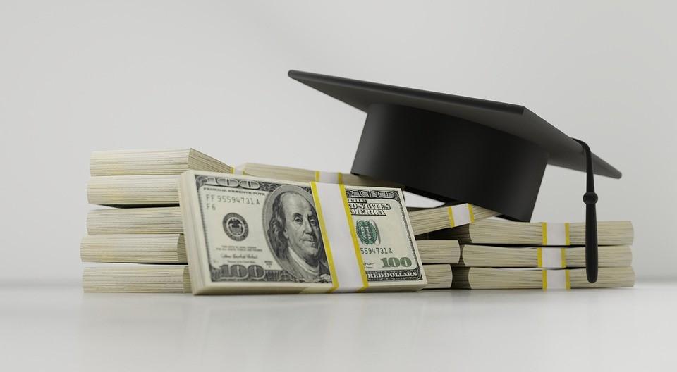 Graduation cap on top of bundles of cash