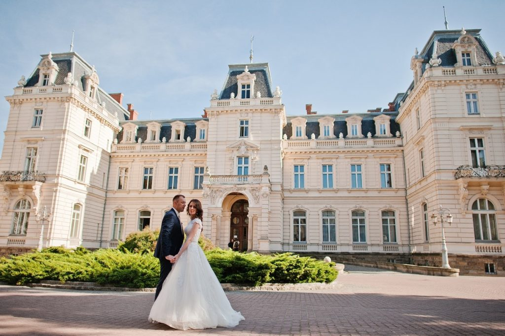 Wedded couple in front of large mansion.