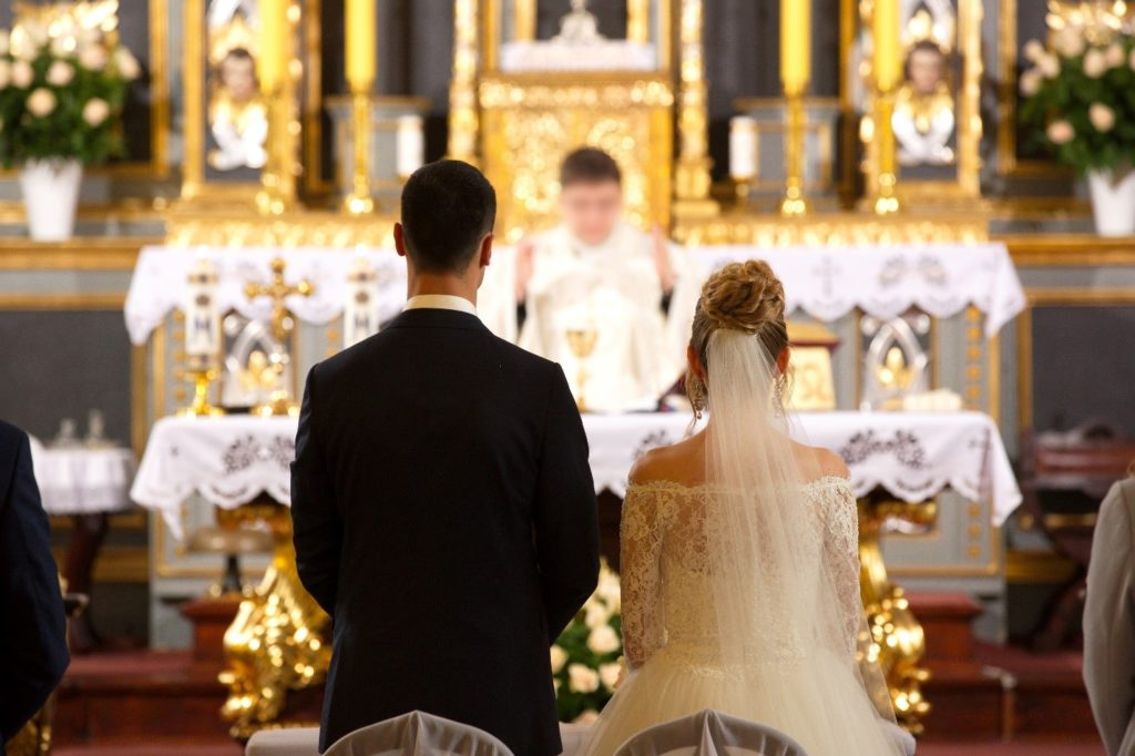 Bride and groom kneeling in front of priest at church.
