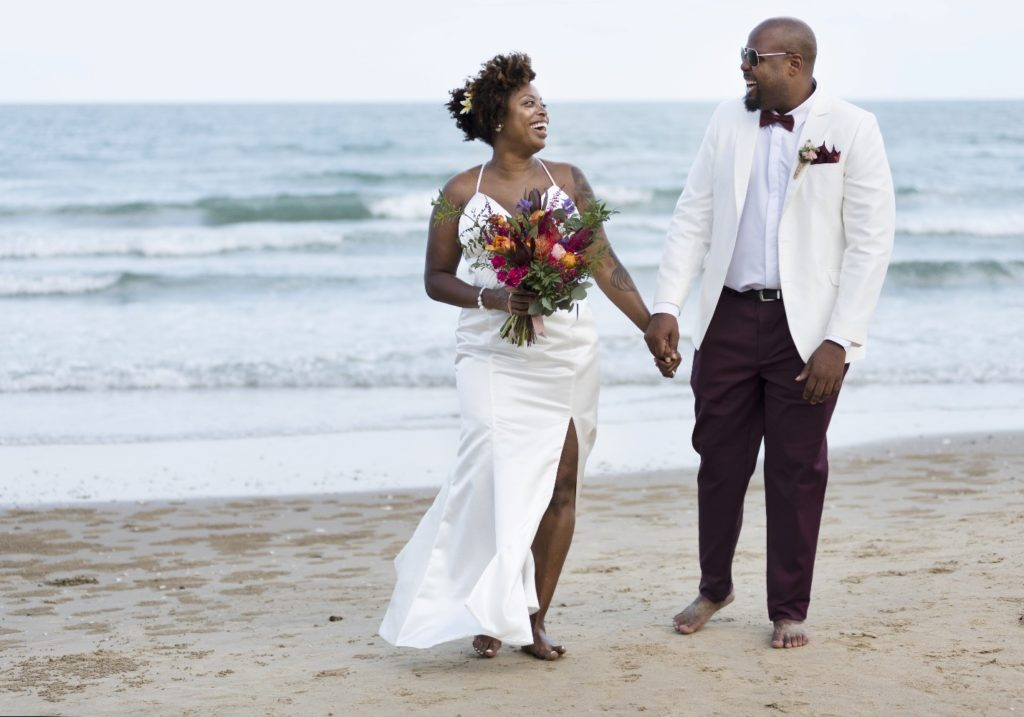 Wedding couple holding hands on a beach.