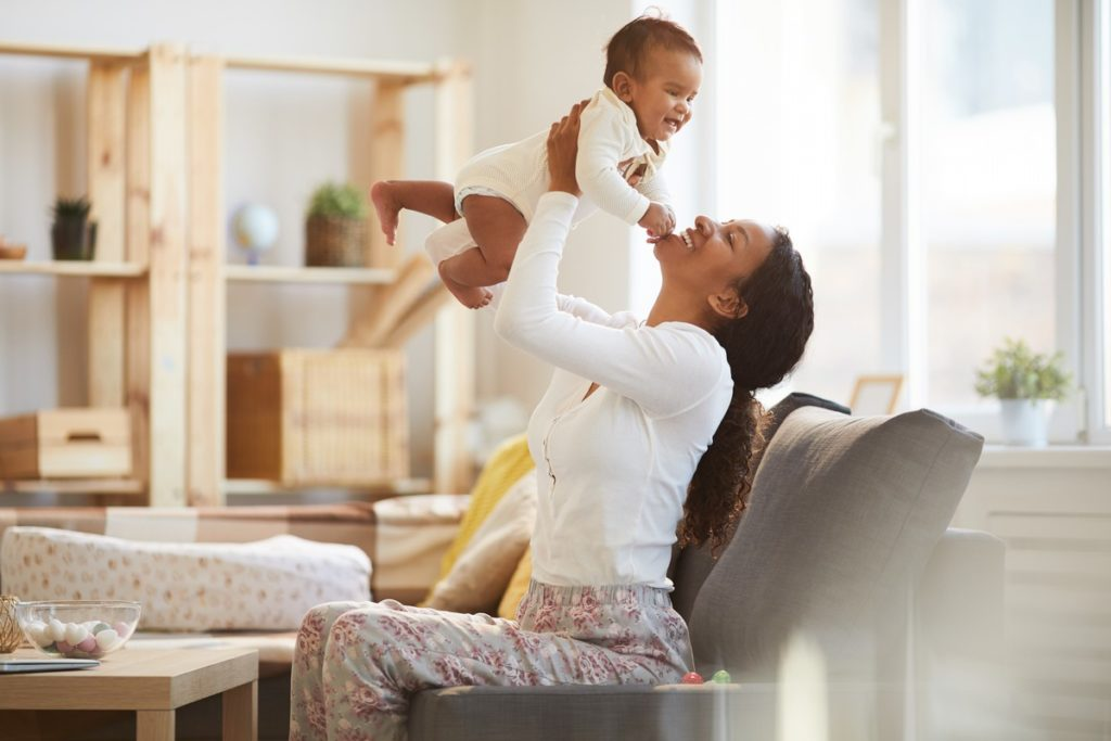 Woman lifting baby into the air.