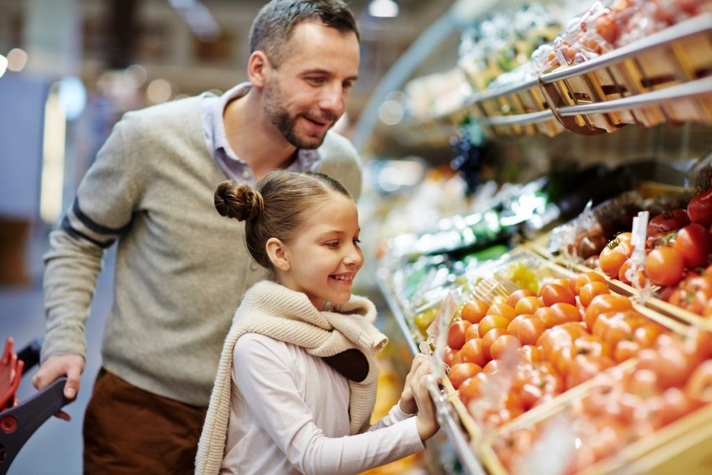 Cute little girl with dad leaning over vegetable counter.