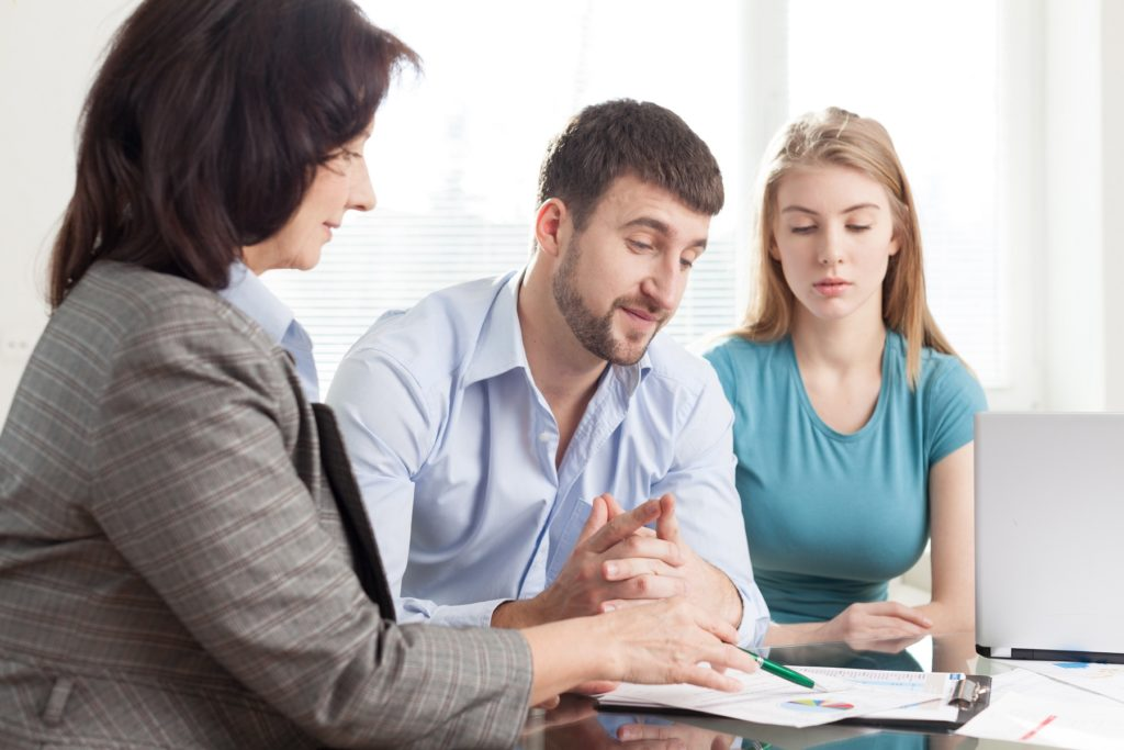 Couple Discussing Paperwork With Financial Consultant