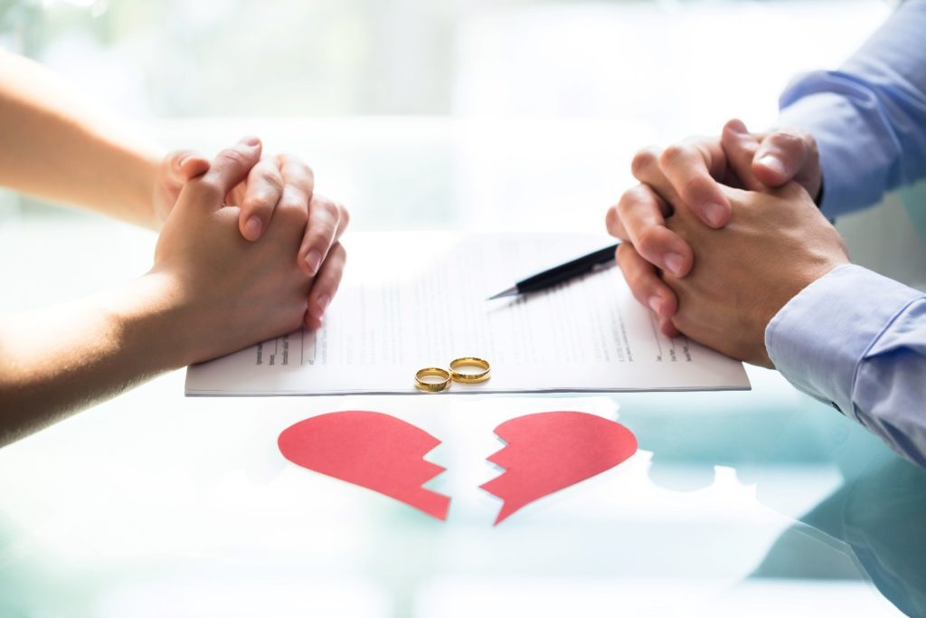 Divorce negotiation between couple - pairs of hands over contract