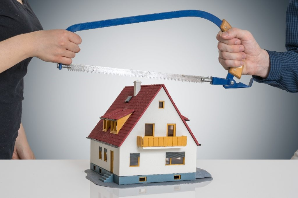 Divorce concept: two people sawing toy house in half