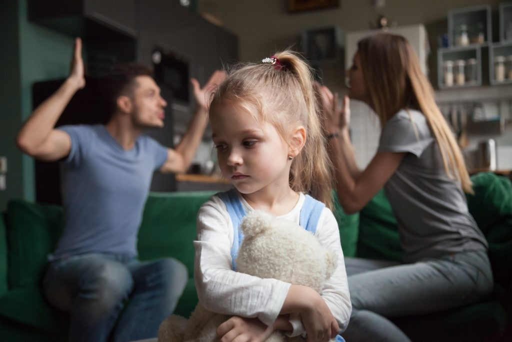 Kid daughter feeling upset while parents fighting at background