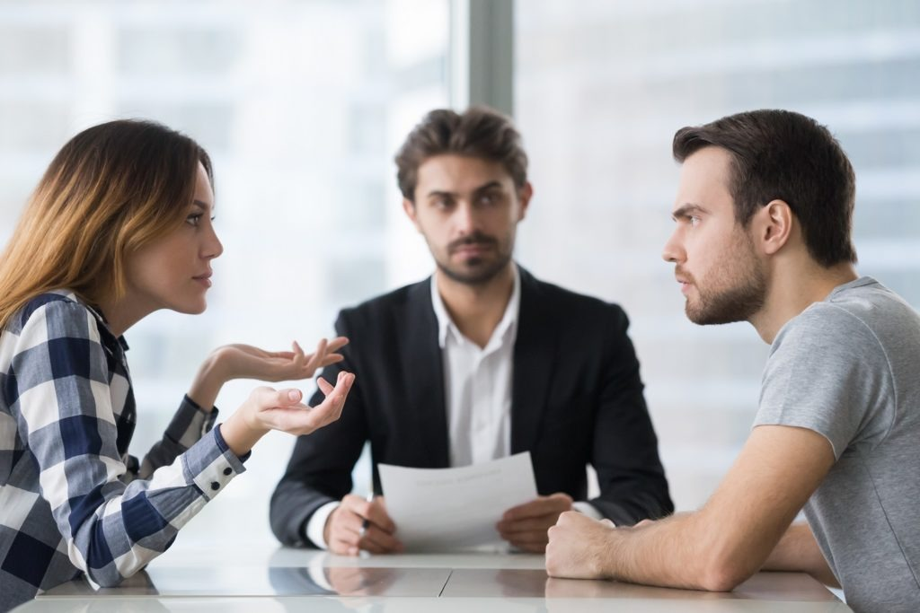 unhappy married couple arguing in lawyers office get divorced