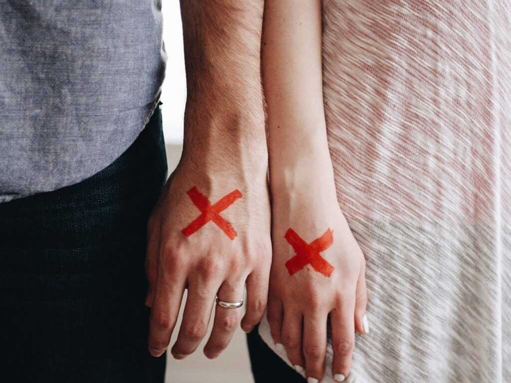 couple standing side by side with red crosses drawn on their hands, representing they're no longer getting along and want a divorce