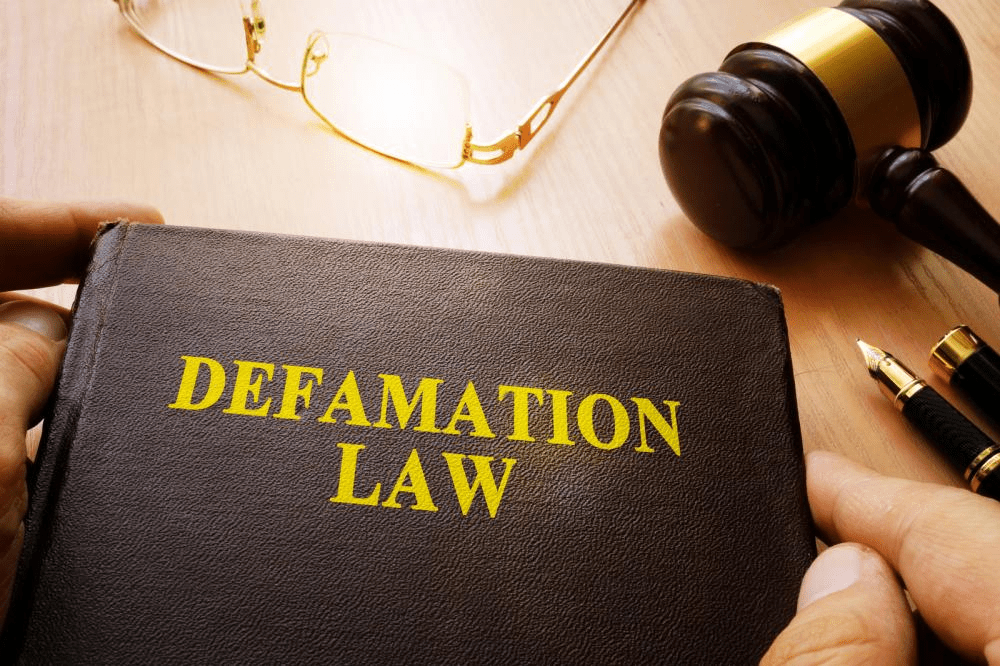 Defamation law book and gavel on a table.