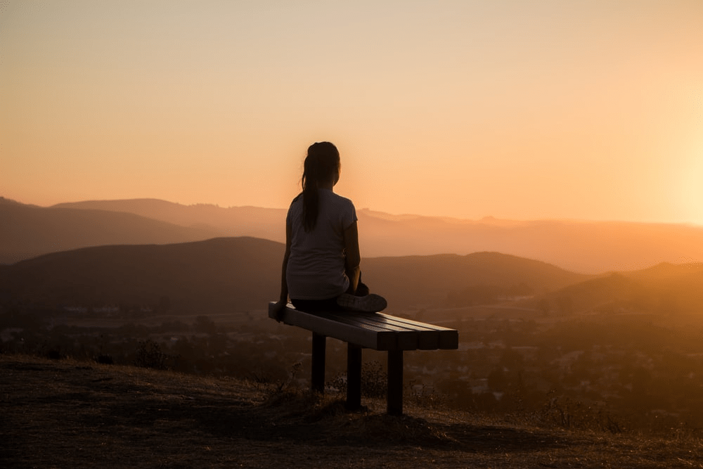 A woman sitting alone on a bench watching a sunset