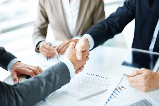 persons shaking hands after drafting a clear and understandable prenuptial agreement.