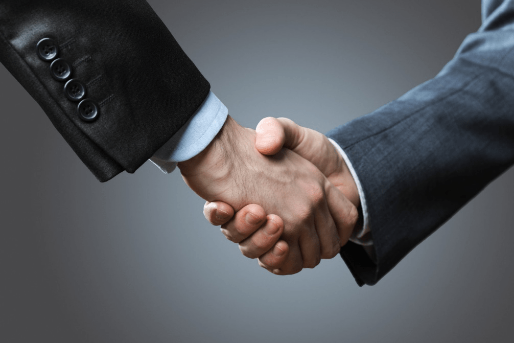 Two business men shaking hands after discussion.