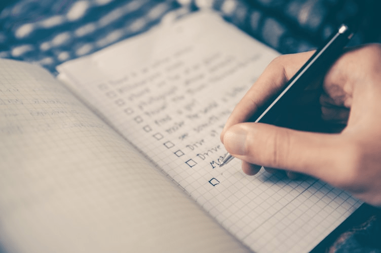 writing down a checklist on his notepad