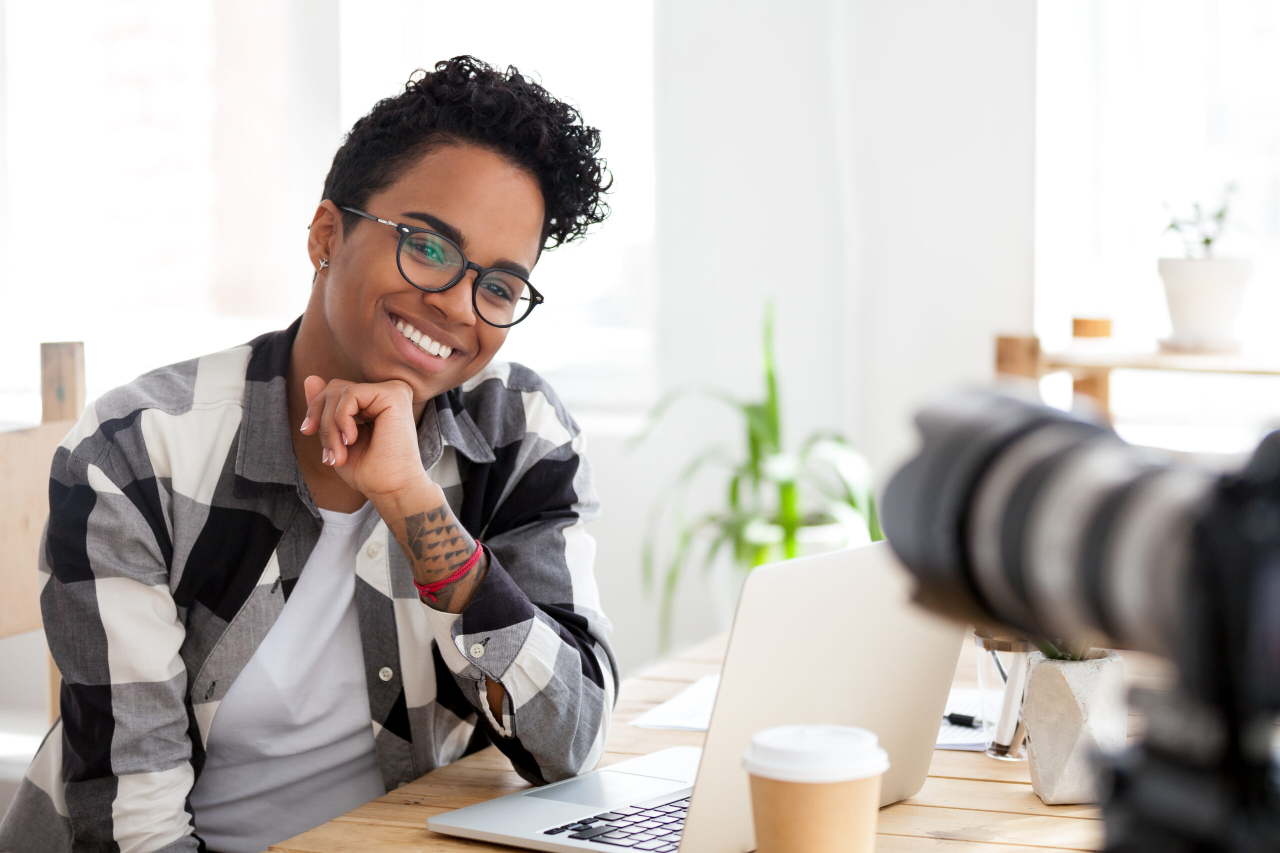 Smiling African American female blogger sit at office desk shooting video, excited black millennial woman look at camera making live broadcast or filming webinar, mixed race girl give interview