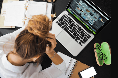 woman looking at laptop in frustration