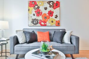 couch and coffee table with flower painting above couch