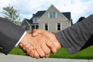 Two men shaking hands in front of house