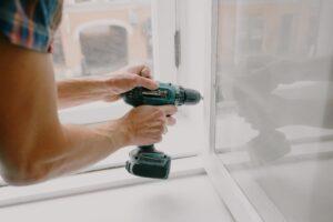 man drilling in window frame