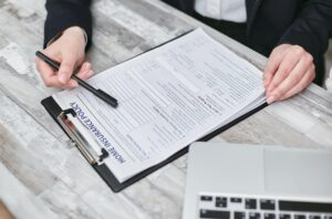 woman looking at form attached to clipboard