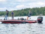 three people on a boat bass fishing