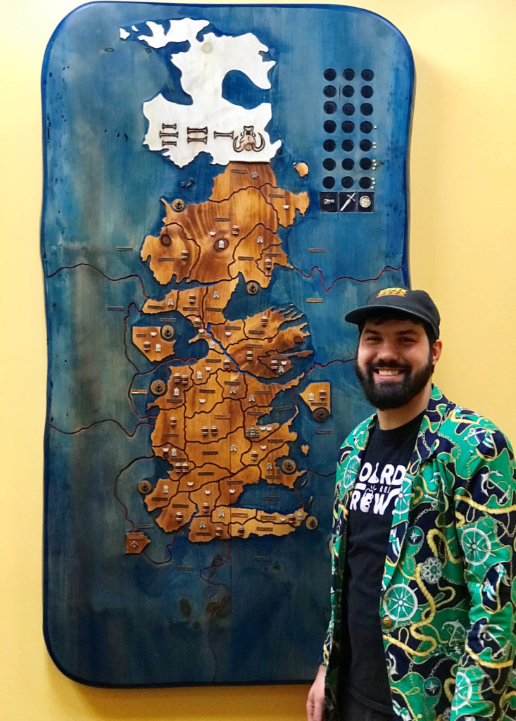 """Co-owner Keating Tufts stands beside his handmade """"Game of Thrones"""" board."""