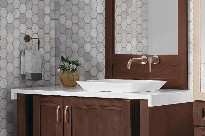 dark walnut bathroom vanity with rose gold hardware, white marble countertop, and gray hex tile walls