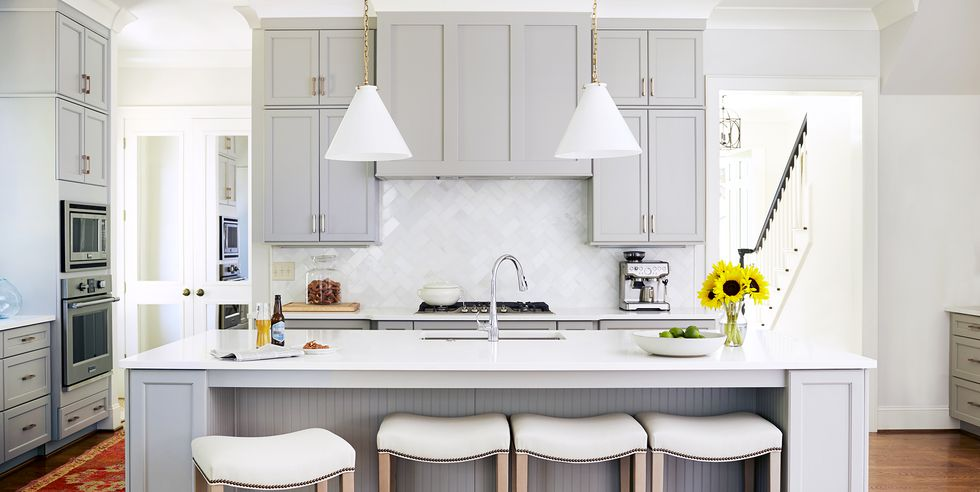 remodeled kitchen with light grey cabinets, white countertops, a rich medium wood floor, and a kitchen vent hood hidden behind faux cabinetry