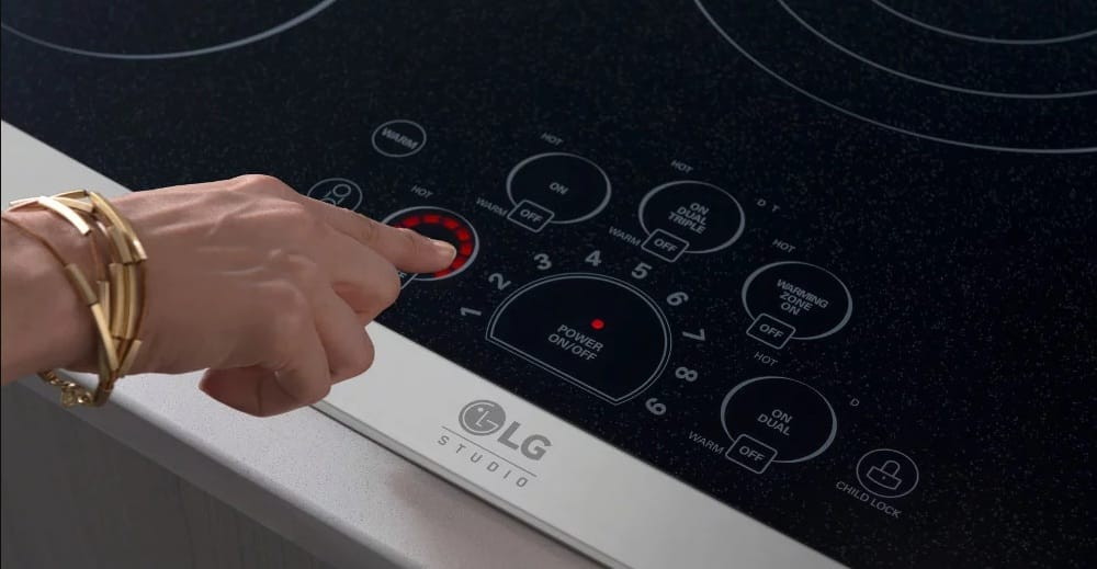 someone operating the touch controls on an LG Studio induction range cooktop