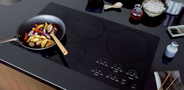 induction range cooktop with vegetables cooking in a non-stick skillet