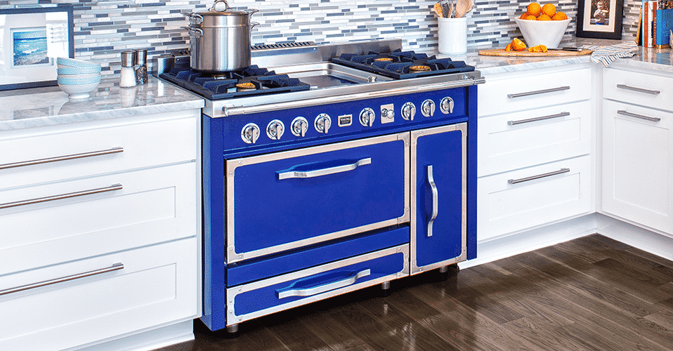 vibrant blue Viking range in a remodeled kitchen with dark wood floors, white cabinets, and grey countertops