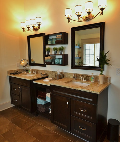 double sinks with storage shelves in between and 4-light fixtures above each vanity