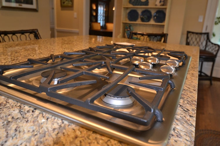 gas stove cooktop built into kitchen island with granite countertops