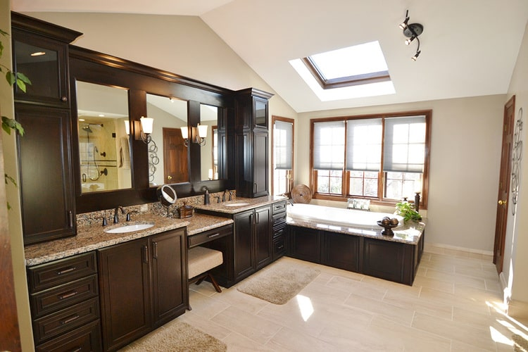 remodeled bathroom with dark cabinets, granite counters, two sinks, a makeup vanity, built-in tub, and skylight